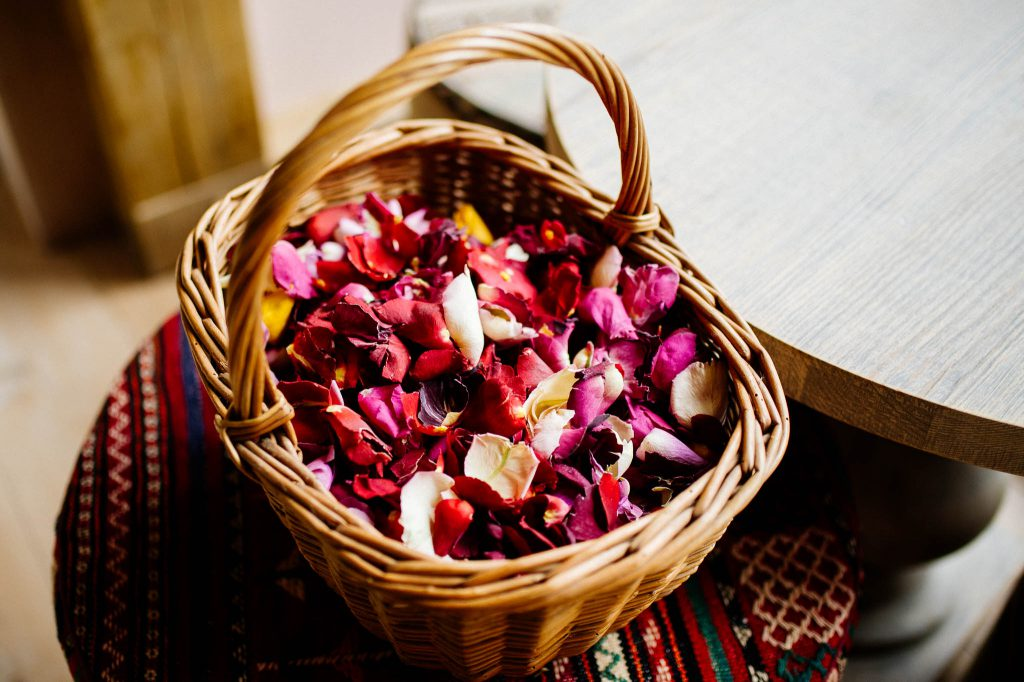 A rattan basket full of real flower petals to be used as confetti at an eco friendly wedding.