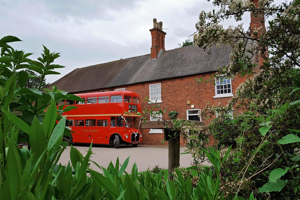 London bus outside a wedding venue waiting to transport guests.